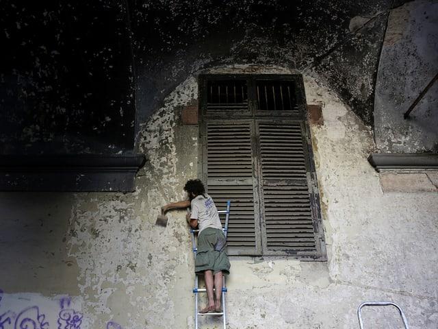 Mann arbeitet an einer Häuserfassade in Turin.