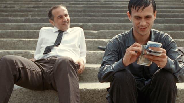 Zwei Männer sitzen auf einer Treppe. Ein älterer mit Hemd und Krawatte lehnt sich lässig nach hinten. Ein jüngerer zählt lächelnd Geldscheine.