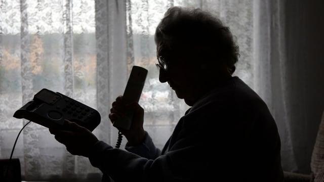 Ene Rentnerin hält ein Telefon in der Hand.