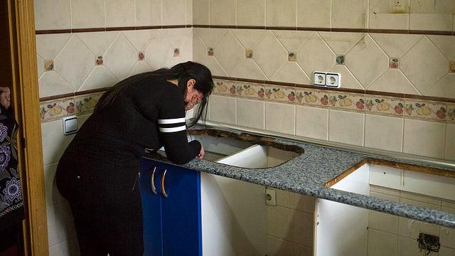 Frau kehrt weinend der Kamera den Rücken. Sie steht in ihrer leer geräumten Küche.
