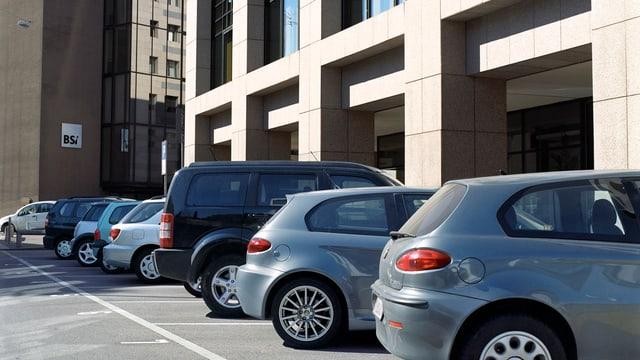 Einige schräg einparkierte Autos vor einem modernen Gebäude, im Hintergrund ein zweiter Neubau.