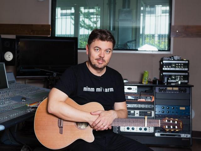 Sänger Padi im Studio mit Gitarre.