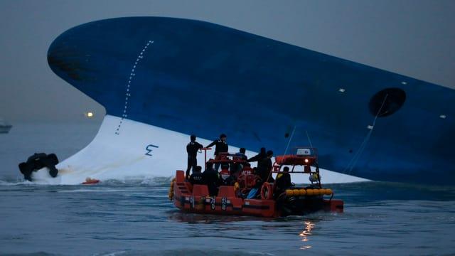 Teil der Fähre ragt aus dem Wasser. Rettungsboot davor.