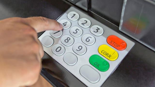 Mann tippt Code am Bancomat ein