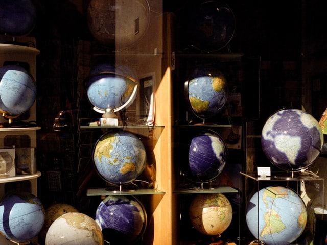 Ein Schaufenster mit einem Regal, in dem alte Weltkugeln stehen.