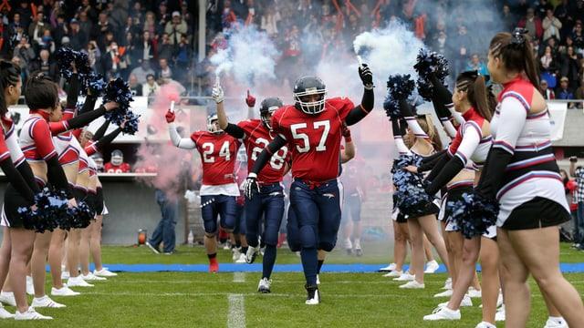 Footballspieler der Broncos laufen ins Stadion ein. Cheerleader stehen Spalier.