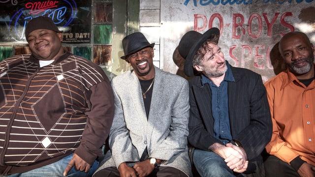 Drei Schwarze und ein Weisser sitzen auf einer Bank vor einer Bar.