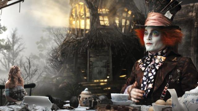 Eine Frau und ein Mann sitzen zum Tee in einer skurrilen Umgebung an einem Tisch. Die Frau ist winzig klein, der Mann erscheint riesig. Der Mann trägt einen Hut und hat rot gefärbte Haare. Die Augen stechen durch ihre giftgrüne Farbe hervor.
