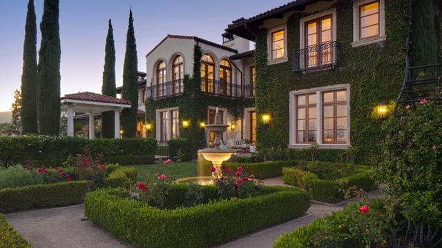 Ein Bild von Heidi Klums Villa mit Garten. Das ganze Anwesen ist mit Efeu bewachsen.