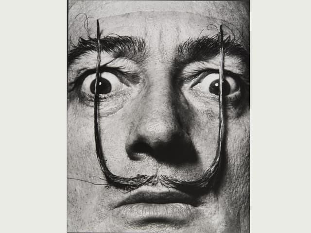 Porträt von Salvador Dali, den Schnauz gerade hoch gezogen vor die Augen, die Augen weit geöffnet.