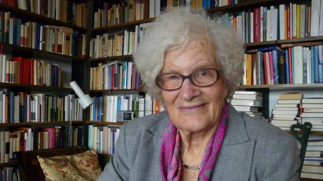 Judith Giovannelli vor ihrem vollen Büchergestell in ihrer Wohnung.