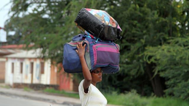 Eine Frau mit viel Gepäck auf dem Kopf