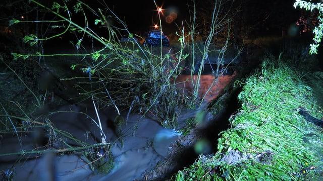 Das weggeschwemmte Fahrzeug (im Hintergrund), im Vordergrund ein reissendes Bächlein und zerdrücktes Gras.