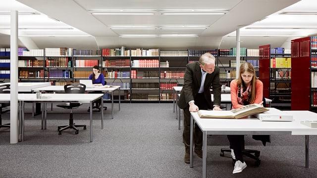Bibliothek mit zahlreichen Tischen, an denen Menschen arbeiten.