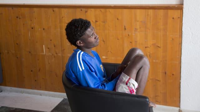 Ein junger Mann sitzt mit angezogenen Beinen auf einem Sessel.
