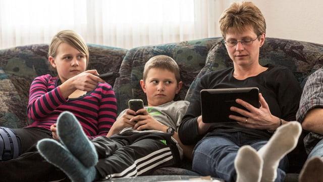 Man sieht eine Familie auf dem Sofa. Ein Kind mit Fernsehbedienung, ein weiteres mit Handy und die Mutter mit Tablet.