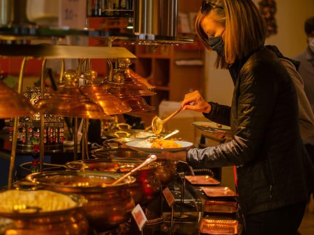 Eine Frau schöpft sich einen Teller voll indisches Essen am Buffet.
