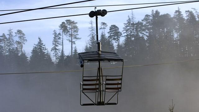 Ein unbesetztes Sesseli auf der Weissenstein-Bahnstrecke, im Hintergrund die Baumwipfel eines Waldes.