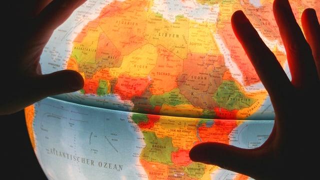 Zwei Hände auf einem erleuchteten Globus, der Afrika zeigt.
