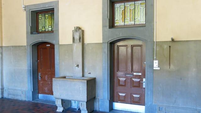 Ein alter Steinbrunnen zwischen zwei alten Türen - Teilansicht eines hundertjärigen Schulhauses.