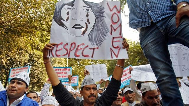 Ein Anhänger der Antikorruptionspartei (AAP) mit einem Plakat und dem Schriftzug: Respect Women