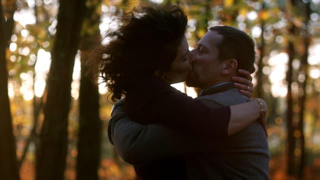 Ein Mann und eine Frau küssen sich im Wald.