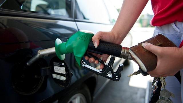 Frau, die einen Tankstutzen in einen Auto-Tank steckt.