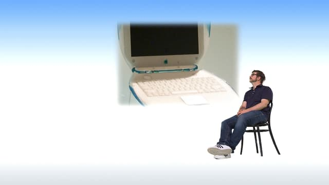 Guido Berger sitzt auf einem Stuhl und schaut ein Bild eines alten Computers an.