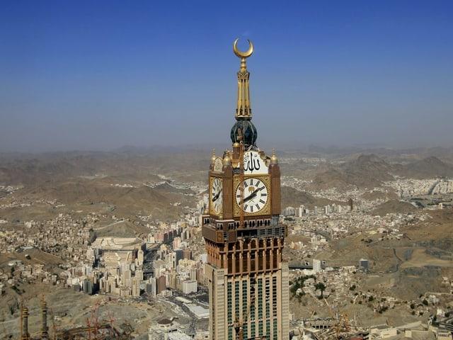 Ein riesiger Turm mit Turmuhr und goldener Mondsichel steht unter blauem Himmel inmiten einer Stadt, die in der Wüste steht.