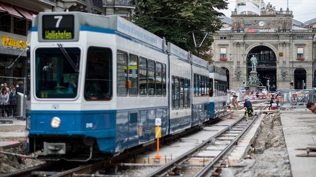 Blauweisse Züri-Tram fährt durch Baustelle vor dem Zürcher Hauptbahnhof