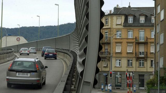 Lärmschutzwand bei der Auffahrt auf die A3 in Zürich-Wiedikon mit Wohnhäusern rechts davon.