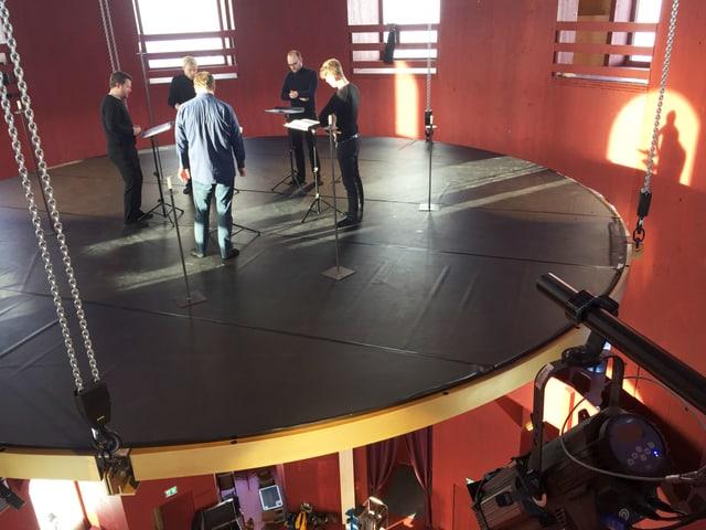 Fünf Männer stehen auf einer runden Plattform