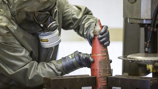Person in Schutzkleidung hantiert mit einem Chemiwaffen-Geschoss.