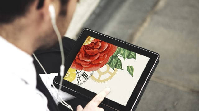 Ein Mann mit Tablet in der Hand klickt auf den Bildschirm.