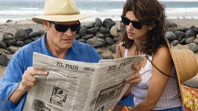 Ein Mann mit Sonnenbrille und Hut liest Zeitung. Eine Frau sitzt neben ihm und liest mit.