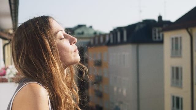 Eine Frau steht auf dem Balkon und richtet ihr Gesicht mit geschlossenen Augen zur Sonne.