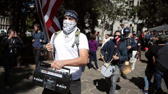 Ein maskierter Mann trägt Amerikaflagge auf einer Demonstration.