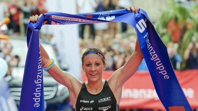 Eine Triathletin hält ein Banner hoch.