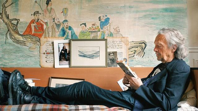 Peter Handke liest auf einem Sofa sitzend ein Buch.