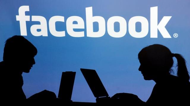 Zwei Menschen am Computer, dahinter Facebook-Logo