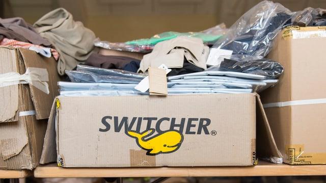 """Offene Kartonschachtel mit der Aufschrift """"Switcher"""" und Kleidern in Plastikverpackungen, die oben herausschauen."""