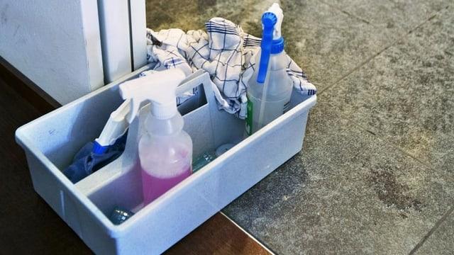 Putzutensilien wie Tuch und Putzmittel stehen am Boden.