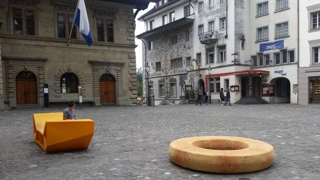 Zwei Sitzgegelegenheiten (Holzring rechts, Kunststoff-Ding links). Im Hintergrund 3 Häauser in der Luzerner Altstadt.