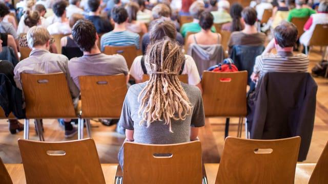 Leute sitzen an einer Versammlung auf Stühlen - Sicht von hinten