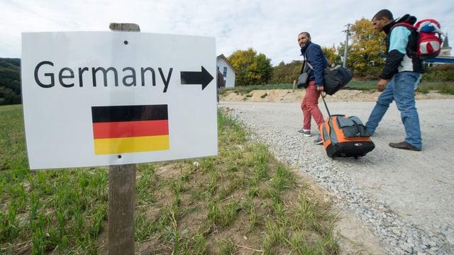 Zwei Flüchtlinge passieren ien Schild mit der Aufschrift «Germany».