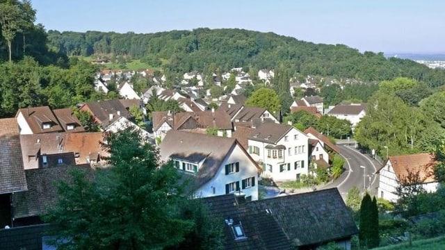 Sicht auf das Dorf, leicht von oben. Man sieht Bäume, Wald und das Dorf.