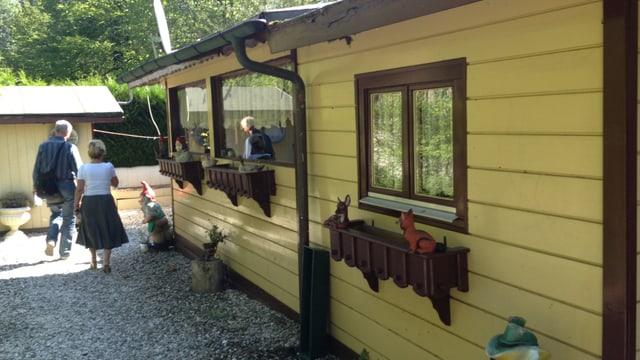 Häuschen aus Holz, mit Blumenkisten und Gartenzwergen.