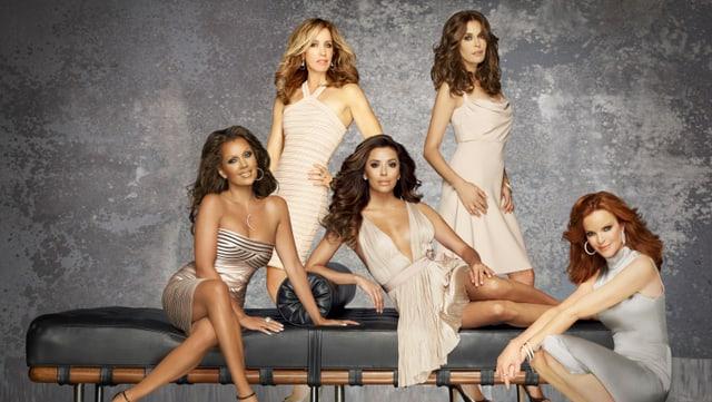 Fünf Frauen posieren auf, vor und hinter einer Lederbank vpor der Kamera. Sie haben alle lange Haare, sind auffällig geschminkt und tragen sexy Kleider.