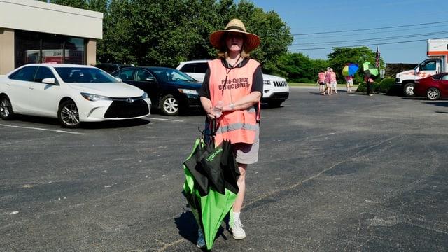 Eine Freiwillige, die Patientinnen auf dem Parkplatz empfängt.