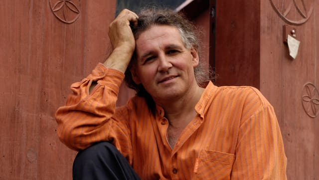Fotografia da Linard Bardill davant l'entrada da ses atelier a Scharàns